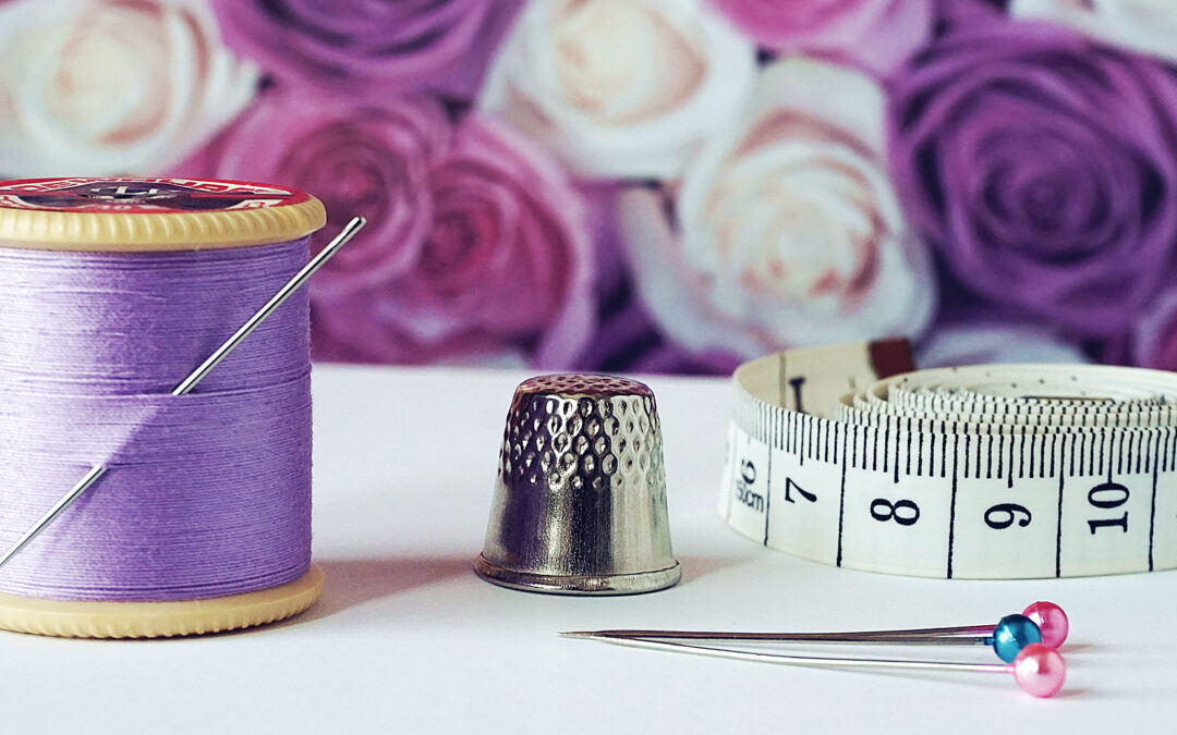 Pic showing a roll of purple thread, thimble, tape measure and pins