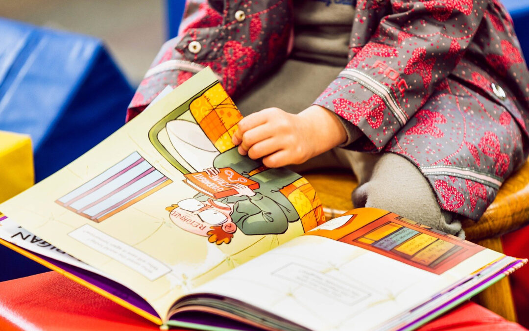 Pic showing a toddlers hands on a kids book